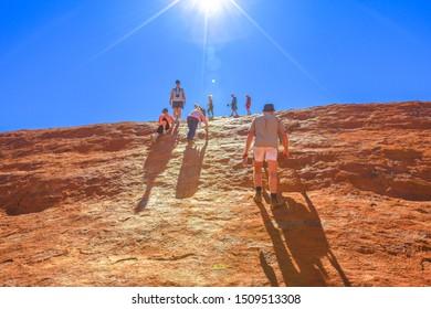 Uluru, Northern Territory, Australia - Aug 23, 2019: people climbing on Ayers Rock before 26 October 2019 when the climb will be closed.Uluru is sacred to Anangu people the owners of Uluru-Kata Tjuta.