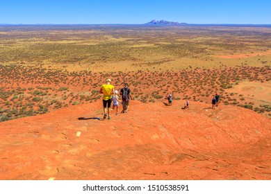 Uluru, Northern Territory, Australia - Aug 23, 2019: people descend along the painted guidelines over top of Ayers Rock in Uluru-Kata Tjuta National Park. Mount Olga rock formation in the distance.