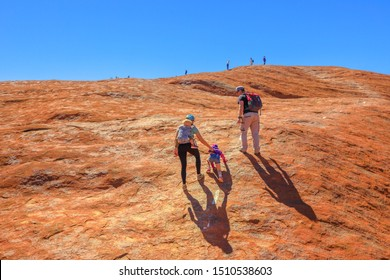 Uluru, Northern Territory, Australia - Aug 23, 2019: family with children climbing on the top of Uluru before October 2019 when the climb will be closed. Uluru - Kata Tjuta is sacred for Anangu people