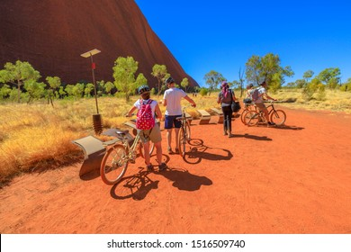 Uluru, Northern Territory, Australia - Aug 24, 2019: people discovery Ayers Rock with Outback Cycling Ride along Kuniya Walk in Uluru-Kata Tjuta National Park, Central Australia. Outdoors activity.
