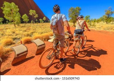 Uluru, Northern Territory, Australia - Aug 24, 2019: couple discovery Ayers Rock with Outback Cycling Ride along Kuniya Walk in Uluru-Kata Tjuta National Park, Central Australia. Outdoors activity.