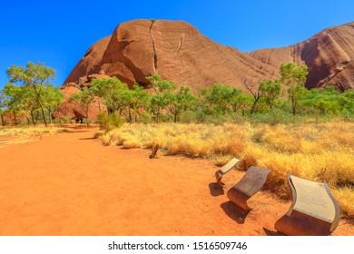 Uluru, Northern Territory, Australia - Aug 24, 2019: Kuniya and Liru Site which tells Uluru's creation stories along Uluru Base Walk in sand path of Uluru-Kata Tjuta National Park, outback landscape.