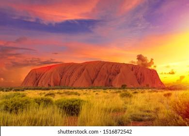 Uluru, Northern Territory, Australia - Aug 22, 2019: Colorful clouds at sunset sky over Ayers Rock in Uluru-Kata Tjuta National Park, Living Cultural Landscape. Majestic australian outback Red Center
