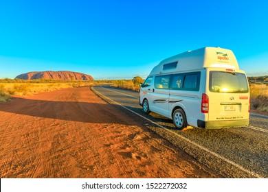 Uluru, Northern Territory, Australia - Aug 25, 2019: campervan car driving on the road leading to Uluru Ayers Rock in Uluru-Kata Tjuta National Park at sunset. Adventure travel in Central Australia.