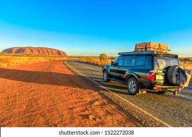Uluru, Northern Territory, Australia - Aug 25, 2019: 4X4 vehicle on the road leading to Ayers Rock, Uluru-Kata Tjuta National Park at sunset. Majestic monolith in Australian outback, Central Australia