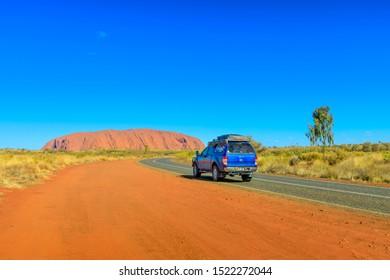 Uluru, Northern Territory, Australia - Aug 25, 2019: 4X4 vehicle on the road leading to majestic monolith of Uluru Ayers Rock in Uluru-Kata Tjuta National Park at sunset. Tourism in Central Australia.