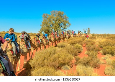 Uluru, Northern Territory, Australia - Aug 22, 2019: Uluru Camel Tours: many people live outback adventure with camel around Uluru landscape on sand dunes of Red Centre in Central Australia.
