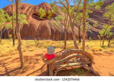 Uluru, Northern Territory, Australia - Aug 26, 2019: Tourist woman with wide hat rest on wooden bench along Uluru Base walk at southern face of Ayers Rock in Uluru-Kata Tjuta National Park.