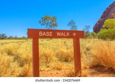 Uluru, Northern Territory, Australia - Aug 26, 2019: Uluru Base Walk sign in sand path of Uluru-Kata Tjuta National Park, outback. Popular base walk is 10 km around circumference of rock track