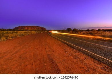 Uluru, Northern Territory, Australia - Aug 25, 2019: Car light trails along the road to Uluru at night. The sandstone monolith icon of Australian outback Red Centre in Uluru-Kata Tjuta National Park.