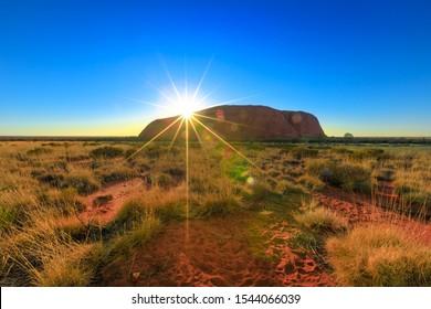 Uluru, Northern Territory, Australia - Aug 24, 2019: Dramatic sunbeams behind the huge Ayers Rock at down monolith. Colors of Uluru sky at sunrise in Uluru-Kata Tjuta National Park.