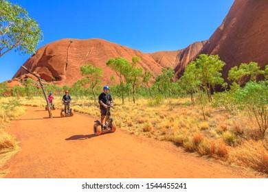 Uluru, Northern Territory, Australia - Aug 24, 2019: people visit Ayers Rock with Uluru Segway Tours along Uluru Base Walk in sand path of Uluru-Kata Tjuta National Park. Outdoors activity.