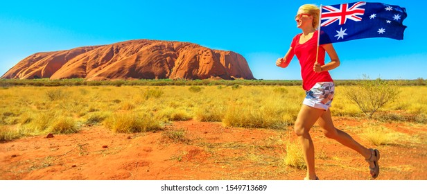 Uluru, Northern Territory, Australia - Aug 25, 2019: Happy lifestyle woman running with Australian flag in Australia outback Red Centre. Uluru monolith in Uluru-Kata Tjuta National Park on background.