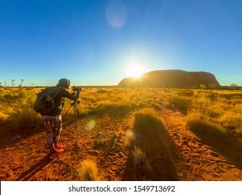 Uluru, Northern Territory, Australia - Aug 25, 2019: Uluru Ayer rock silhouette at sunrise. Photographer taking pictures with tripod in Uluru-Kata Tjuta National Park. Sun rays in Australian outback.