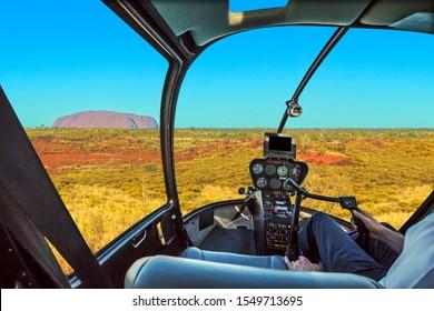 Uluru, Northern Territory, Australia - Aug 25, 2019: Scenic flight over Uluru. Helicopter cockpit aerial view of monolith rock formation in Uluru-Kata Tjuta NP. ILLUSTRATIVE EDITORIAL.