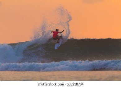 Uluwatu, Bali, Indonesia - July, 31, 2014: A surfer sprays water while surfing at sunset in Bali, Indonesia.