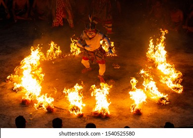 Uluwatu, Bali / Indonesia - March 16 2017: A Kecak (a form of Balinese dance) dancer performing the fire dance and enacting an episode of Hindu mythology Ramayana