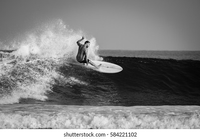 Uluwatu, Bali, Indonesia - October 1, 2015: A surfer carves on a wave while surfing in Uluwatu, Bali.