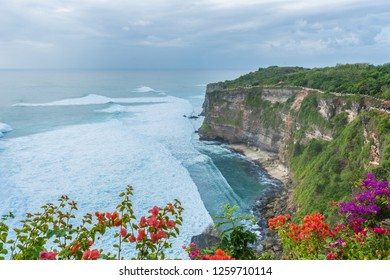 Uluwatu Temple in Bali, Indonesia; at a cloudy sunset. Bougainvillea flowers at the foreground.