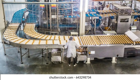 ULYANOVSK, RUSSIA - APRIL 19, 2017. Women in uniform controlling the work of huge conveyor machine producing spice cakes at the confectionary plant