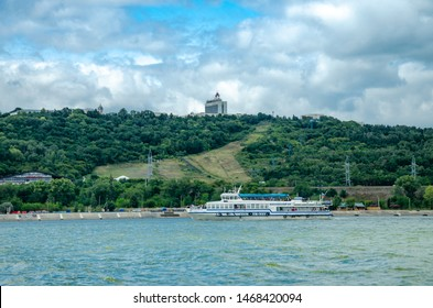 Ulyanovsk, Russia - July,28,2019:  Pleasure boat on the background of the high Volga coast and the view of Ulyanovsk. View from Volga.