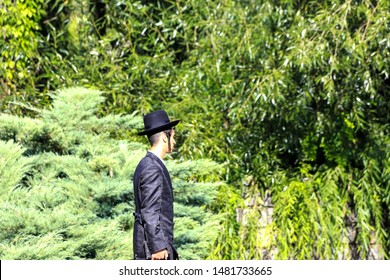 Uman, Ukraine 11.09 2018. A young Jew Hasid boy in  traditional black clothes stands in Uman park , the time of the Jewish New Year, religious Jew