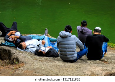 Uman, Ukraine 23, 09 2017. Young men, Hasidim Jews resting on a big stone in Sophia's park during the Jewish New Year.