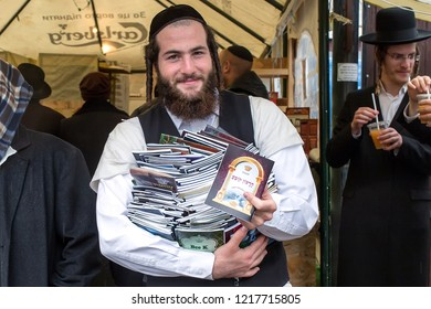 Uman,Ukraine, 13.09.2015: Jewish man with a pile of books in his hands outdoors