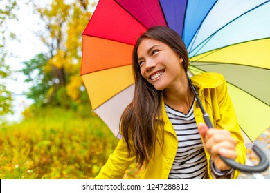 Umbrella Autumn Fashion lifestyle Asian woman under colorful umbrella on fall rainy day , happy girl enjoying walk under the rain in forest with yellow leaves.