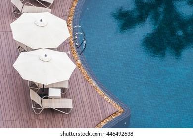 Umbrella and chair around beautiful luxury outdoor swimming pool in hotel resort