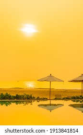 Umbrella and chair around outdoor swimming pool in hotel resort at sunrise or sunset time