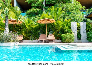 Umbrella and chair around swimming pool in hotel and resort - Holiday Vacation concept