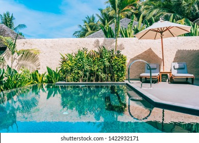 Umbrella and chair around swimming pool neary beautiful landscape of sea ocean beach with blue sky and white cloud for leisure travel and vacation