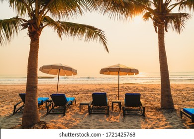 umbrella chair beach with palm tree and sea beach at sunrise times - vacation and holiday concept