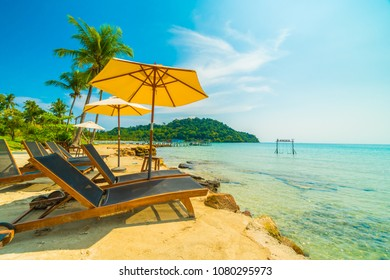 Umbrella and chair on the Beautiful tropical beach and sea with coconut palm tree in paradise island for travel and vacation