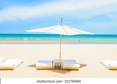 Umbrella and chair on the beautiful tropical beach and sea