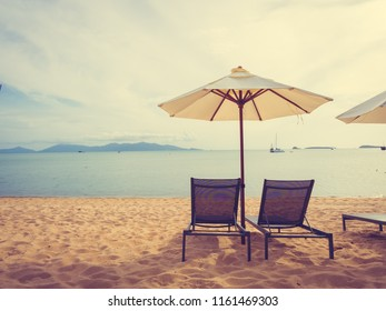Umbrella and chair on the tropical beach sea and ocean at sunrise time for travel and vacation