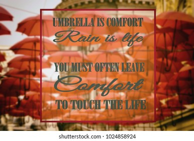 Umbrella is comfort, rain is life! You must often leave comfort to touch the life. Umbrellas in the background, blurred image, motivation, poster, quote.