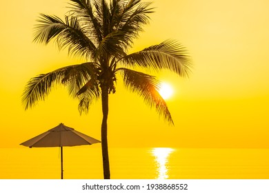Umbrella and deck chair around beach sea ocean with coconut palm tree at sunset or sunrise for leisure vacation