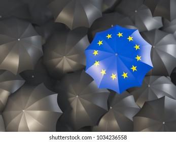 Umbrella with flag of european union on top of black umbrellas. 3D illustration