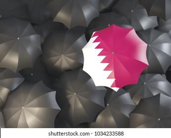 Umbrella with flag of qatar on top of black umbrellas. 3D illustration