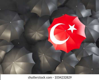 Umbrella with flag of turkey on top of black umbrellas. 3D illustration