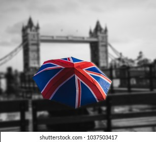 ?olored umbrella in the form of British flag (selective focus), on a black and white background of a bridge in London across the River Thames