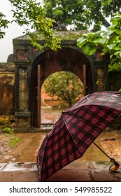 An umbrella in front of an ancient gate at a rainy day at a temple around Hue in Vietnam