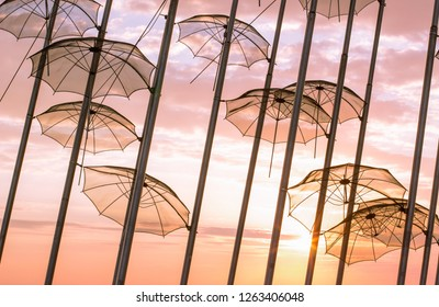 umbrella in high pillar silhouette exterior design on bright pink and orange evening sunset sky background landscape, romantic atmosphere