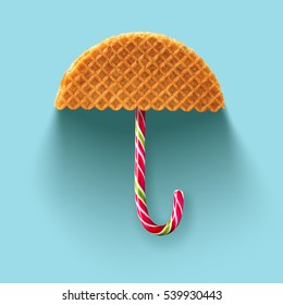 Umbrella made of waffle and Christmas candy on a blue background