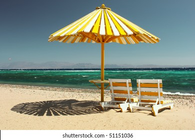 Umbrella on beach with chairs