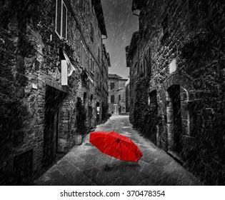 Umbrella on dark narrow street in an old Italian town in Tuscany, Italy. Raining. Black and white with red