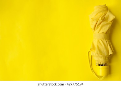 Umbrella on the right side of a yellow background, folded umbrella