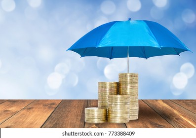 Umbrella  protection coins savings a business. Protection money concept.